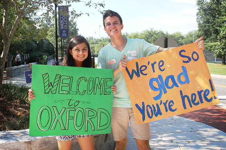 Two students greet arriving students with welcome signs